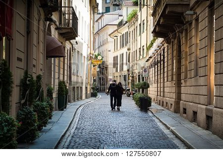 Milan, Italy - September 5th 2015: a couple walking down a quaint street in central Milan.