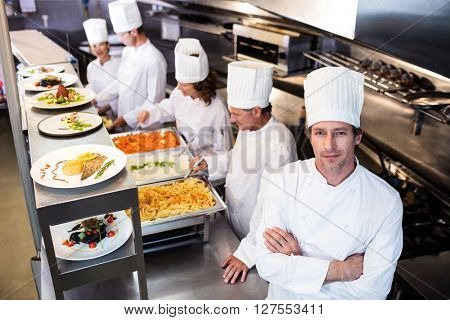 Portrait of chef in commercial kitchen and four chef serving at order station