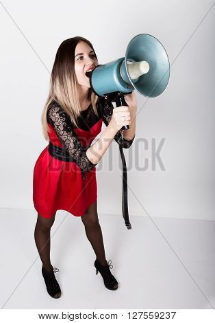 leggy beautiful girl in a red dress with lace sleeves, she yells into a bullhorn. Public Relations.