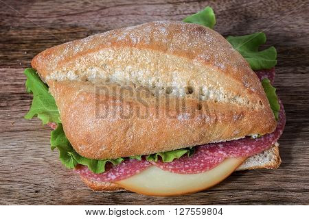 sandwich salami, fontina and salad on wooden table