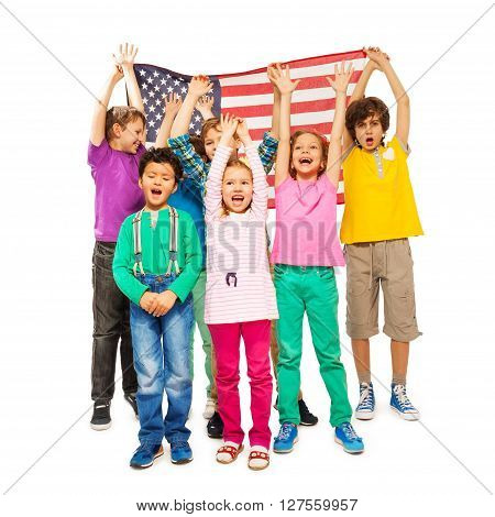 Group of happy age-diverse children enveloped under American flag isolated on white background