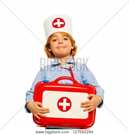 Close-up portrait of young boy with medical cap and toy first-aid kit. isolated on white