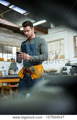 A carpenter is looking at his phone in a dusty workshop