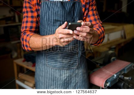 Carpenter is looking at his phone in a dusty workshop