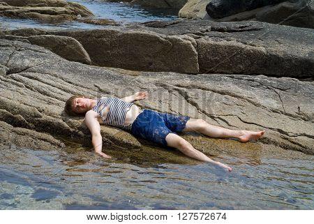 The boy in old striped vest lies on reefs in sea.