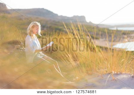 Relaxed woman enjoys reading on beautiful sandy beach.  Young lady with book in her hand. Concept of happiness, enjoyment and well being.  Enjoying Sun on Vacations.