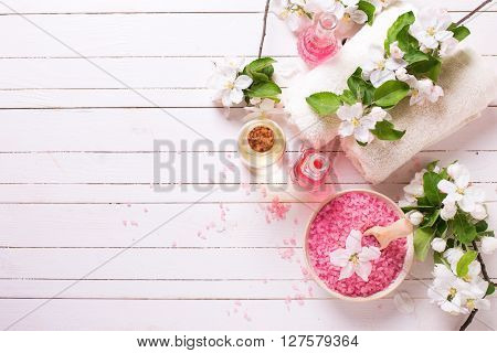 Spa or wellness setting. Pink sea salt in bowl bottles with aroma oil towels and flowers on white wooden background. Selective focus. Place for text.