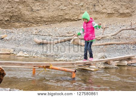 Seven-year Girl Is Gently Moved Across The Creek On The Makeshift Bridge
