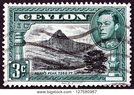 SRI LANKA - CIRCA 1938: a stamp printed in Sri Lanka shows View of Adam's Peak and Portrait of King George VI, circa 1938