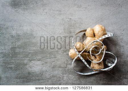 Ginger With Measure Tape On Concrete Background