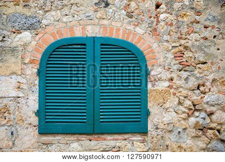 Blue shutters in a medieval stone wall in the Tuscan village of Monteriggioni Italy. Eye catching colors and texture. Concepts could include travel architecture Europe others. poster