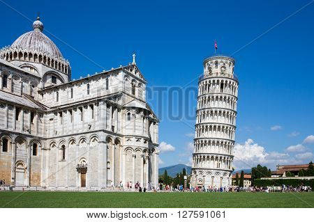 Pisa, Italy - August 2, 2015:  Tourists visiting the Leaning Tower of Pisa and Pisa Cathedral in Italy.  The Tower of Pisa is one of Italy's most iconic tourist attractions and is famous worldwide for its unintended tilt.