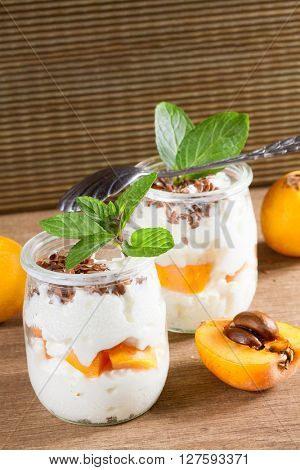 Fresh yogurt with  loquats on rustic background