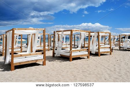 Some beds and sunloungers in a beach club in a white sand beach in Ibiza, Spain