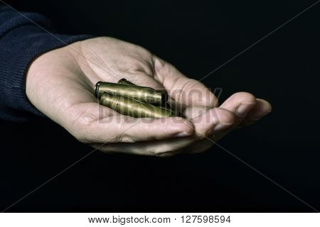 Man with some empty bullets in his hand, against a black background