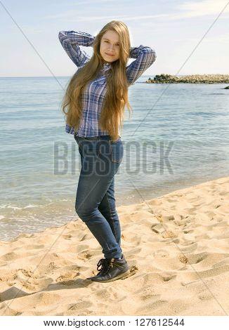 Young beautiful girl sixteen years European long brown hair standing on sandy sea beach.