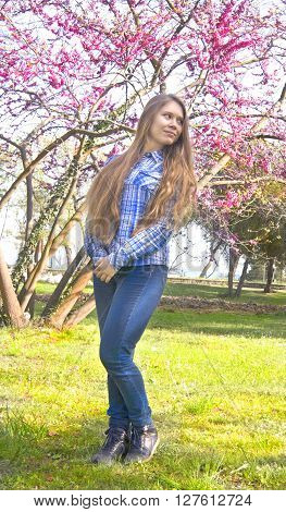 Young beautiful girl European long brown hair in jeans and skirt sixteen years stands near pink cercis tree in park.