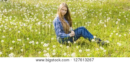 Young beautiful girl sixteen European with long brown hair in jeans and skirt sits on meadow with white dandelions