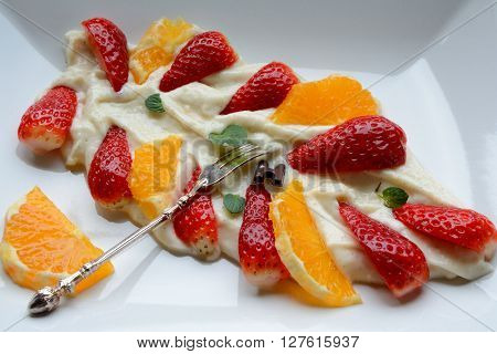 Tasty dessert made of millet gruel with fruits on white plate with silver old vintage fork