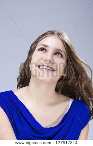 Dental Concepts and Ideas. Caucasian Female Teenage Girl With Teeth Brackets. Posing in Studio Environment and Happy Smiling. Vertical Image