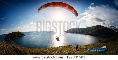 Skydiver flying over the water during sunset with the mountains