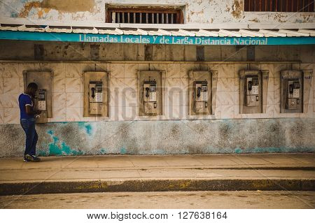 CUBA in December 2015: A male person uses a public payphone to make a call. Public phones are the only telephones for many people in Cuba, international calls are expensive.