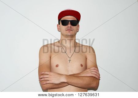 topless naked joung man in a baseball cap and sunglasses
