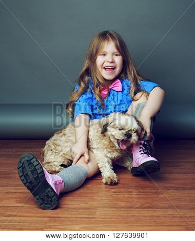 happy girl with her dog in the studio against grey background