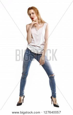 sexy young blonde topless in jeans playfully posing on a white background with naked breasts