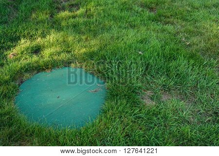 Septic system lid in a backyard lawn
