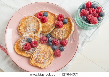 Fresh buttermilk pancakes with berries and sugar
