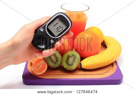 Hand with glucose meter fresh ripe natural fruits and glass of juice on cutting board concept for diabetes healthy nutrition and strengthening immunity