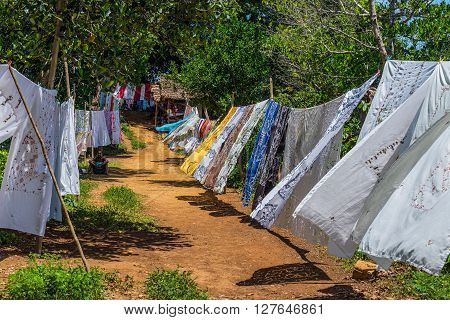 Ampasipohy Nosy Be Madagascar - December 19 2015: Selling embroidered tablecloths in the rural village of the Ampasipohy Nosy Be Island Madagascar. Emboitered tablecloths is the traditional craft of this region.