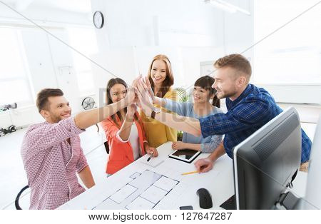 business, startup, architecture, gesture and people concept - happy international creative architect team or students with blueprint making high five at office poster