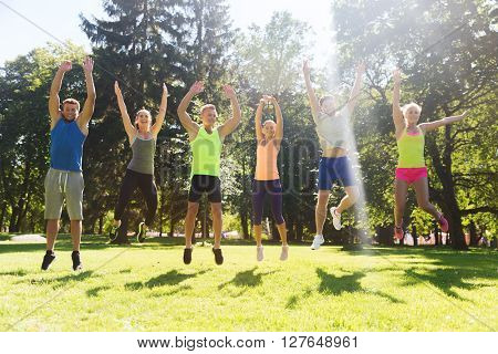 fitness, sport, friendship and healthy lifestyle concept - group of happy teenage friends or sportsmen jumping high outdoors