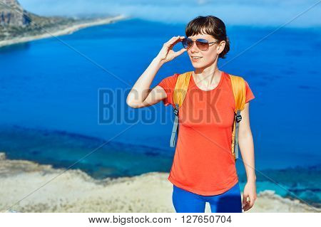 female traveler with backpack  standing on the trail against sea and blue sky at early morning