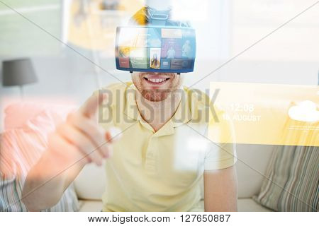 technology, multimedia, mass media, entertainment and people concept - happy young man in virtual reality headset or 3d glasses with media or web applications at home