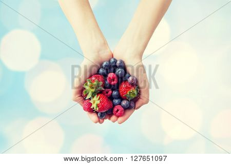 healthy eating, dieting, vegetarian food and people concept - close up of woman hands holding different ripe summer berries over blue lights background