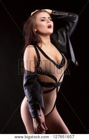Woman In Leather Jacket And Body Lingerie Posing Sexy On Black Background