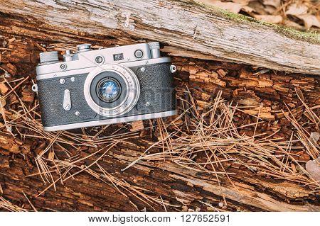 35mm Vintage Old Retro Rangefinder Camera On Old Fallen Wood Tree In Forest.