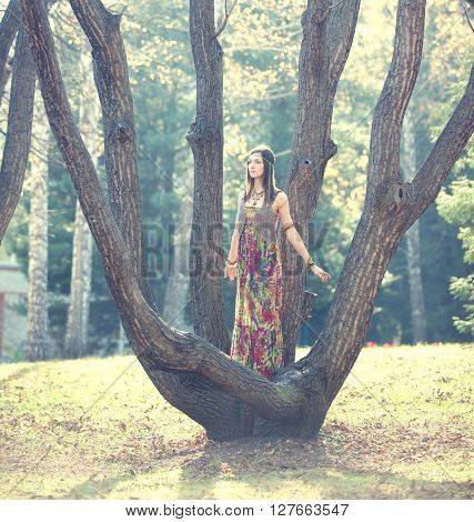 Hippie girl standing among the branches of a tree