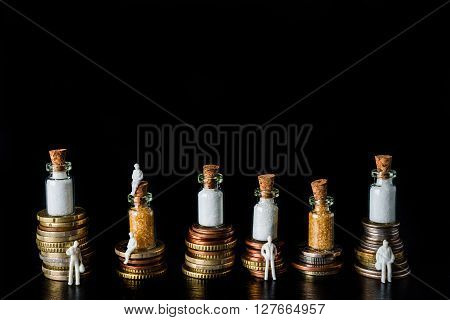 Piles of coins with sugar cubes and bottles filled with sugar on top symbolising sugar tax on black slate background with white people figures