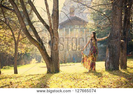 Girl in autumn park near the house
