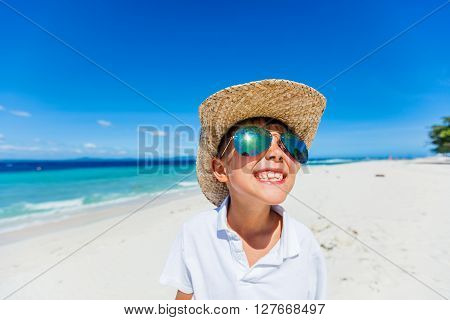 Portrait of a boy in the sunglasses and hat on the tropical white beach