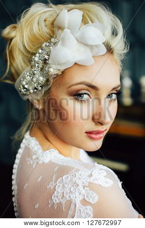 Gorgeous fashionable bride. Blonde hair. Hairdresser salon stylist trendy bright make-up. Pretty woman posing on background of piano looking at camera. Stylish hair accessories. Close up portrait