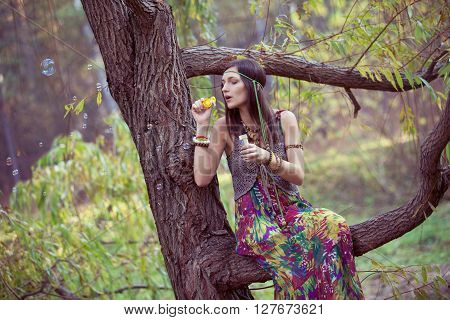 Hippie girl on a  tree branch blow bubbles