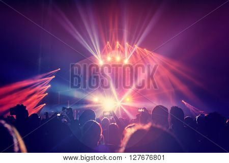 Large group of a happy young people enjoying concert, having fun spending time in a night club, dancing in bright laser beams, men partying, celebrating holidays