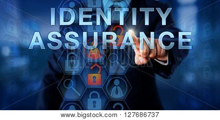 Administrator pressing IDENTITY ASSURANCE on an interactive touch screen display. Information technology metaphor and online concept for the ability to verify the validity of electronic credentials.