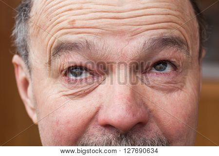 Emotions at the older man's face. Elements of gymnastics for the eye to improve vision