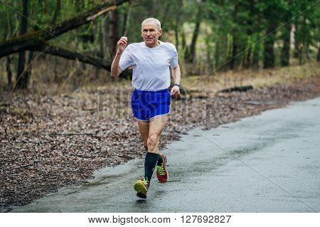 Chelyabinsk Russia - April 23 2016: elderly male runner athlete running in Park on way during Half marathon in woods